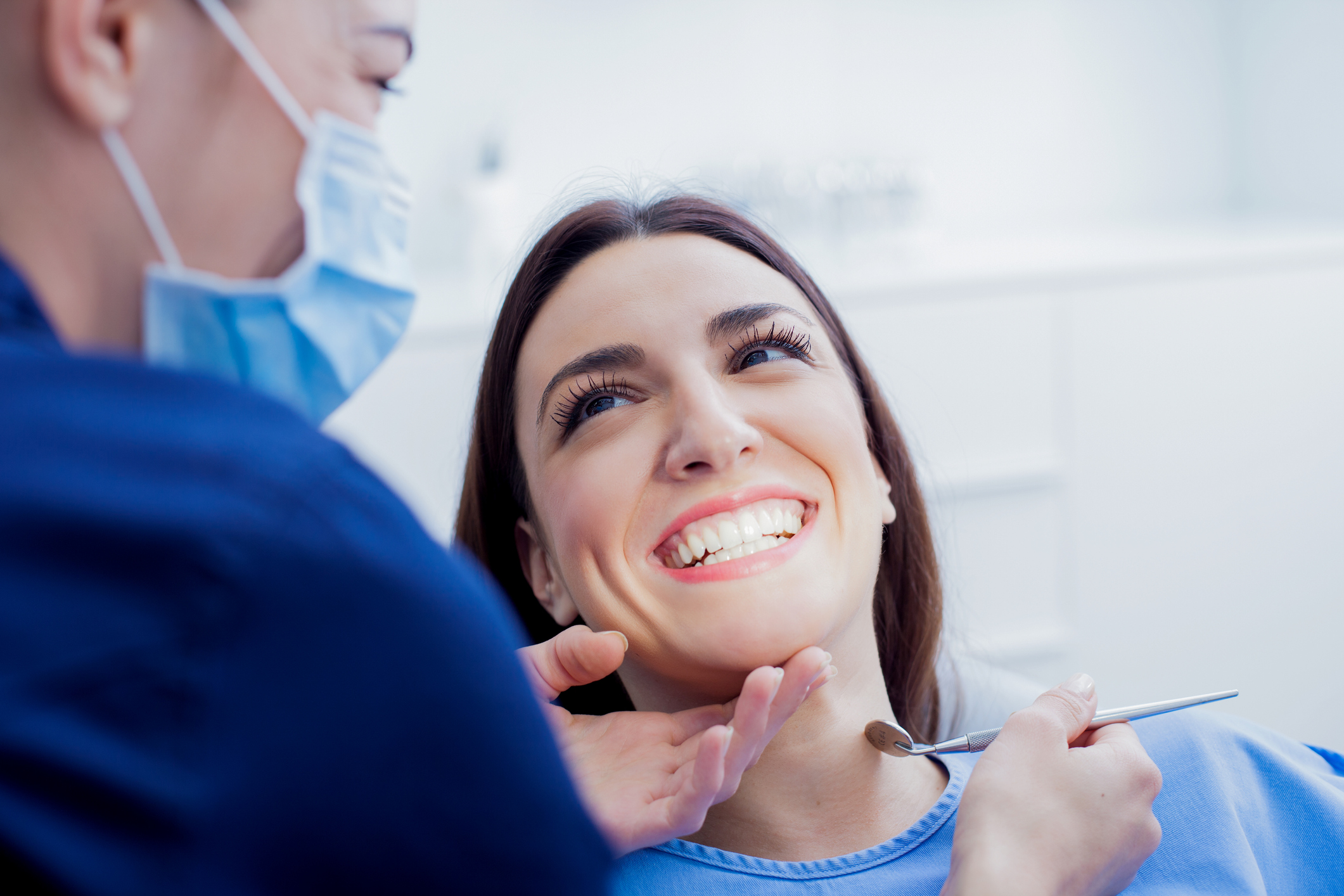 A female patient getting her teeth professionally cleaned at a dentist's office.