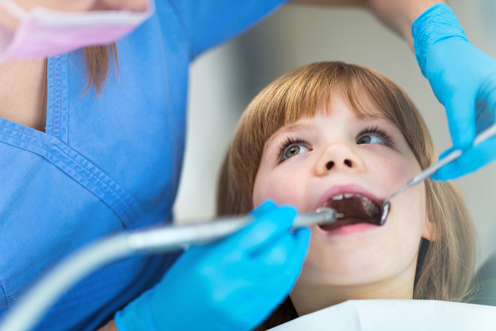 A young girl sitting in a dentist's chair receiving a routine check up and teeth cleaning.
